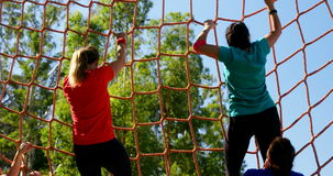 Female trainer assisting women in climbing net during obstacle course stock video