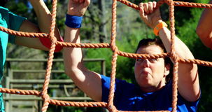 Female trainer assisting women in climbing net during obstacle course stock video footage