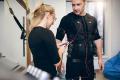 Female trainer connecting cables on sportsman ems suit. Portrait of female trainer connecting cables on sportsman ems suit Stock Images