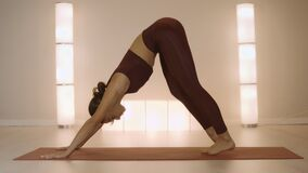 Trainer doing upward facing dog pose. Woman performing yoga poses in studio