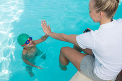 Female trainer giving high five to boy Stock Photos