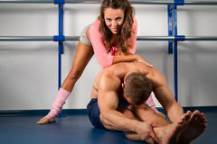 Female trainer helping guy Royalty Free Stock Photo
