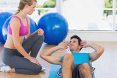 Female trainer helping man with his exercises at gym Royalty Free Stock Images