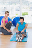Female trainer helping man with his exercises at gym Royalty Free Stock Photo