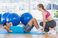 Female trainer helping man with his exercises at gym Stock Images