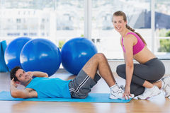 Female trainer helping man with his exercises at gym Royalty Free Stock Photography