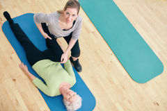 Female trainer helping senior woman do leg stretches at rehab. High angle view of female trainer helping senior women do leg stretches at rehab. Gym trainer Stock Photo
