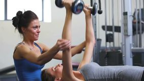 Female trainer helping woman lift weights. At gym stock footage