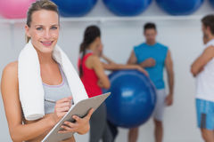 Female trainer holding clipboard with fitness class in background Stock Photography