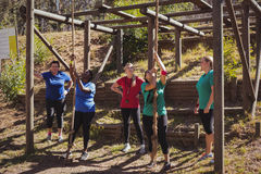 Female trainer instructing women in climbing a rope in the boot camp Royalty Free Stock Image