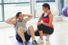 Female trainer looking at man do abdominal crunches Stock Image