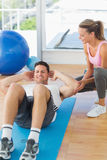 Female trainer looking at young man do abdominal crunches Stock Images