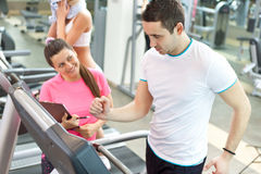 Female trainer with man on treadmill stock images
