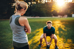 Female trainer in the park with man working out stock photos