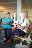 Female trainer with senior in gym Stock Photography