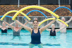 Female trainer and senior swimmers exercising with pool noodle. Portrait of female trainer and senior swimmers exercising with pool noodle Stock Photo