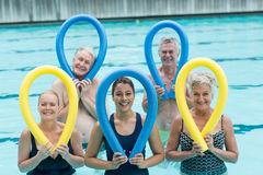 Female trainer and senior swimmers holding pool noodles. Portrait of female trainer and senior swimmers holding pool noodles Stock Photo