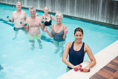 Female trainer with senior swimmers standing in pool Royalty Free Stock Image