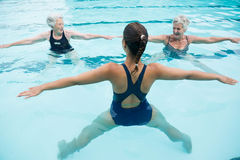 Female trainer with senior women exercising in swimming pool Stock Photos