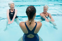 Female trainer with senior women exercising in swimming pool. Smiling female trainer with senior women exercising in swimming pool Stock Image
