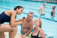 Female trainer showing time to senior swimmers at poolside. Young female trainer showing time to senior swimmers at poolside Royalty Free Stock Image
