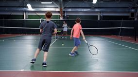 A female trainer in a sports suit teaches playing tennis in two middle-aged boys, guys are bouncing balls on a tennis stock video footage
