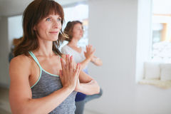 Female trainer with student doing Vrikshasana Royalty Free Stock Images
