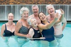 Female trainer taking selfie with senior swimmers in pool. Young female trainer taking selfie with senior swimmers in pool Royalty Free Stock Image