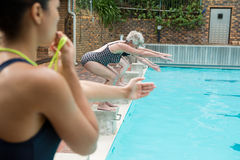 Female trainer whistling while senior women diving into pool Stock Images