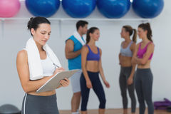 Female trainer writing on clipboard with class in background Royalty Free Stock Photos