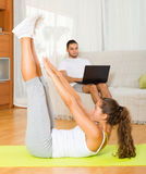 Female training on mat and inert guy resting Royalty Free Stock Images