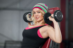 Female trains in gym with dumbbells Stock Photography