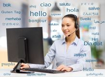 Female translator over words in foreign languages. Translation, business and technology concept - smiling female translator or operator with computer at office stock image
