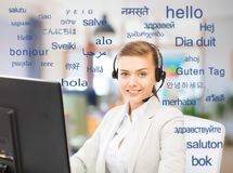 Female translator over words in foreign languages. Translation, business and technology concept - smiling female translator or operator with computer at office royalty free stock images