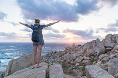 Female traveler, arms rised to the sky, watches a beautiful sunset on spectacular rocks of Capo Testa, Sardinia, Italy. Royalty Free Stock Photos