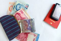 Female Traveler in asia concept. Confusion with currencies! - A concept photograph showing a female cloth canvas purse with assorted currency bank notes from royalty free stock photo