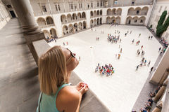 Female traveler on the background of Arcades in Wawel Castle in Cracow. Poland. Renaissance Stock Images