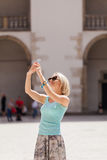Female traveler on the background of Arcades in Wawel Castle in Cracow. Poland. Renaissance. A woman is photographed on her phone against the background of the Royalty Free Stock Photography
