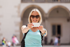 Female traveler on the background of Arcades in Wawel Castle in Cracow. Poland. Renaissance. A woman is photographed on her phone against the background of the Royalty Free Stock Image