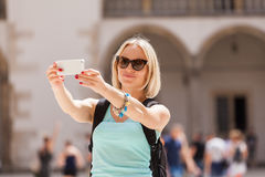 Female traveler on the background of Arcades in Wawel Castle in Cracow. Poland. Renaissance. A woman is photographed on her phone against the background of the Stock Image