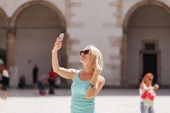 Female traveler on the background of Arcades in Wawel Castle in Cracow. Poland. Renaissance. A woman is photographed on her phone against the background of the Stock Images