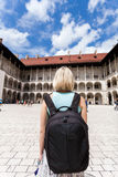 Female traveler on the background of Arcades in Wawel Castle in Cracow. A woman in a blue T-shirt with a backpack on her back is standing in the courtyard of Royalty Free Stock Photo