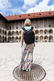 Female traveler on the background of Arcades in Wawel Castle in Cracow. A woman in a blue T-shirt with a backpack on her back is standing in the courtyard of Royalty Free Stock Image