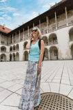 Female traveler on the background of Arcades in Wawel Castle in Cracow. A woman in a blue T-shirt with a backpack on her back is standing in the courtyard of Stock Images