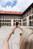 Female traveler on the background of Arcades in Wawel Castle in Cracow. A woman in a blue T-shirt with a backpack on her back is standing in the courtyard of Stock Photos