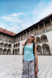 Female traveler on the background of Arcades in Wawel Castle in Cracow. A woman in a blue T-shirt with a backpack on her back is standing in the courtyard of Royalty Free Stock Photos