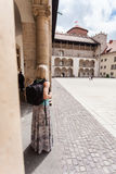 Female traveler on the background of Arcades in Wawel Castle in Cracow. A woman in a blue T-shirt with a backpack on her back is standing in the courtyard of Stock Photo