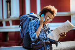 Female traveler with backpack speaking on phone, looking at map.