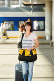 Female traveler with duffel bag and suitcase at train station Royalty Free Stock Images
