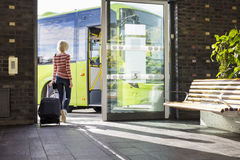 Female traveler going on the bus at terminal Stock Images
